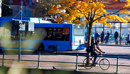 A bus and cyclist at the bus terminal.